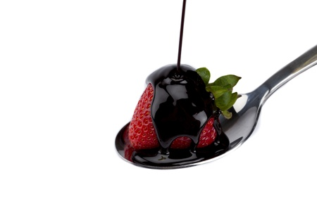Horizontal image of a strawberry dripping with chocolate syrup in a metal spoon photo