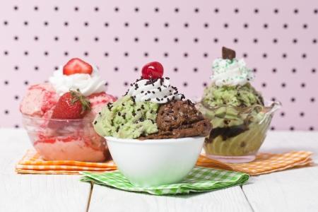 coppa di gelato: Tre gusti di gelato in una ciotola con diversi condimenti Archivio Fotografico