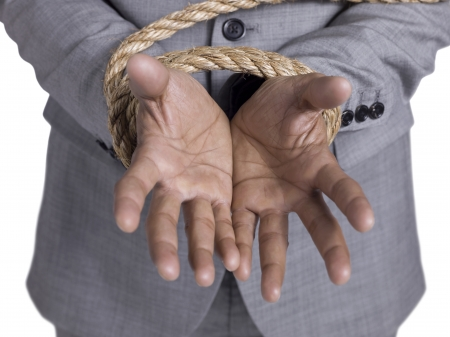 Close-up hand of a businessman tied with rope isolated on a white surface photo