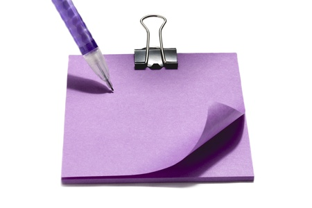 ball pen: Horizontal image of a violet sticky note slightly curled up, with black binder clip and violet ball pen