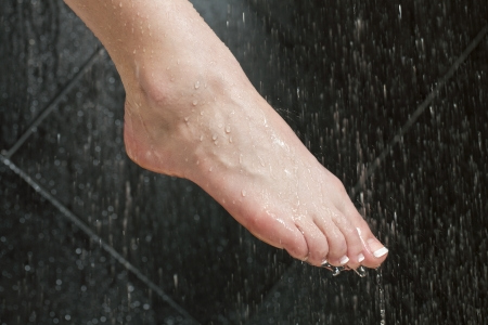 disinfect: Close up image of woman washing her feet under the running water Stock Photo