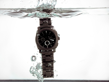 Wrist watch fallen into the water creating water bubbles and splashes