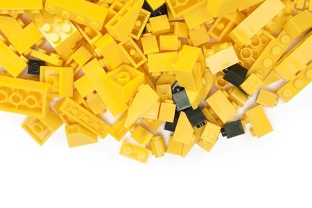 흰색 배경에 노란색과 검은 색 레고 블록의 이미지를 닫습니다