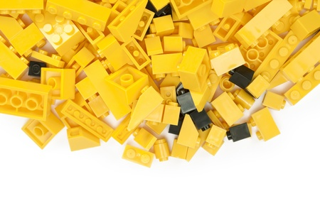 yellow lego block: Close up image of yellow and black lego blocks against white background