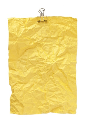 Close-up image of a yellow rumpled paper with a metal clip isolated on a white background Stock Photo