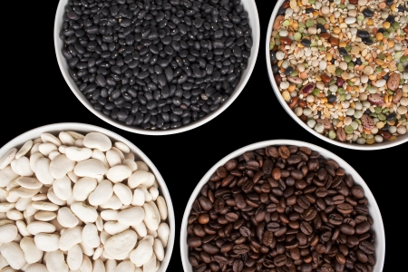 Close-up cropped shot of variety of food grains in bowls.