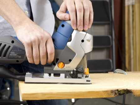 Close-up image of a person cutting wooden sheet with jigsaw. Stock Photo - 17258423