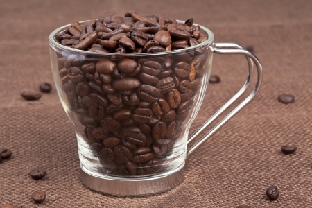 caffeine molecule: Close-up shot of pile of coffee beans in coffee mug while some scattered on table cloth.