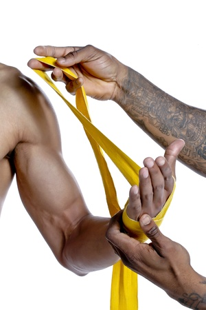 Close-up image of a man putting bandage on the boxer's hand against white background Stock Photo - 17396112