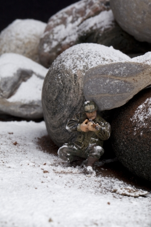 Soldier hiding on the rocks and targeting someone with his rifle on a winter season Stock Photo - 17258399