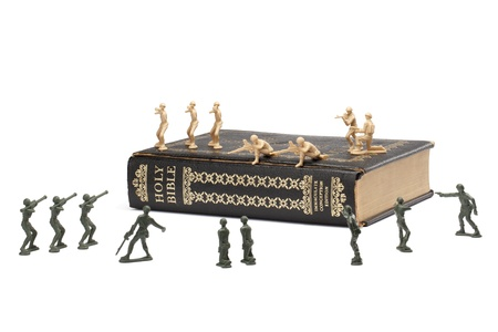 Image of toy soldiers and Holy Bible fighting over the white surface