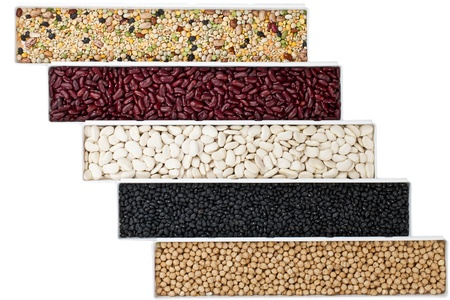 protein crops: Overhead shot of various food grains in rectangular containers on white surface.