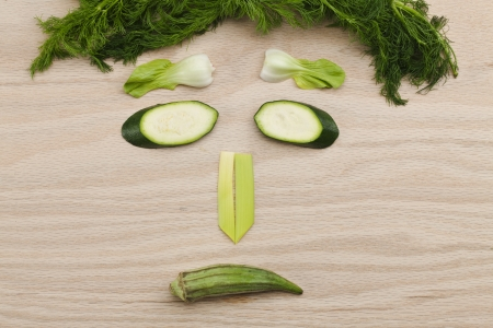 Vegetable face on wooden surface photo