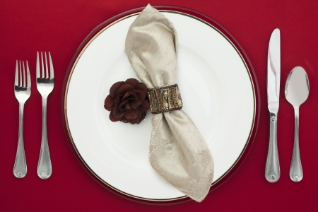 Overhead shot of a dinner table with silverware, napkin, plate and a flower. photo