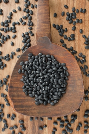 Vertical image of spilled black beans on a wooden spoon on the table Stock Photo - 17258549
