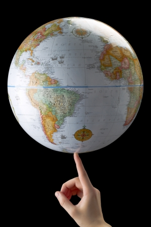 Human finger spinning a globe Stock Photo