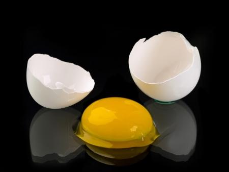 crack: A raw white egg cracked against black background