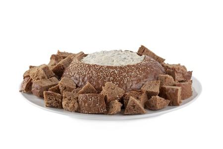 pumpernickel: Płyta chleba pumpernikiel i dip szpinakiem na białym powierzchni