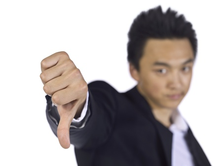 disapprove: Disagreeing businessman gesturing a thumbs down over a white background