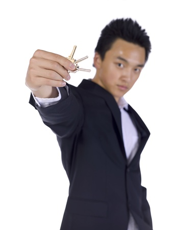 Young businessman showing keys over a white background Stock Photo - 17288238