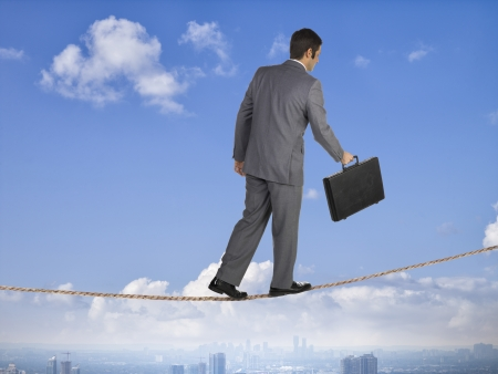 inconstant: Image of business man balancing on a rope in the sky Stock Photo
