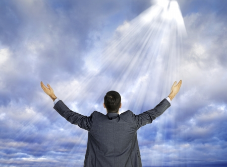 Rear view of a businessman with hands raised while sun rays falling on him from sky. photo