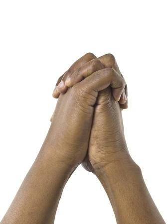 manos orando: Imagen de primer plano de las manos humanas juntos contra la superficie blanca