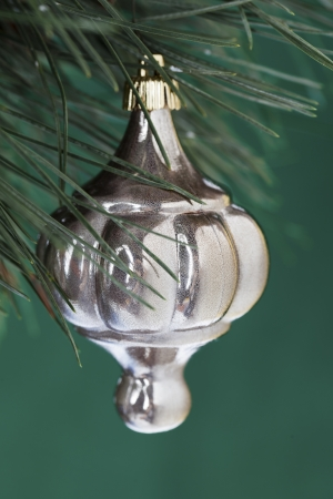 refle: Shiny Christmas bauble hanging on Christmas tree over green background. Stock Photo