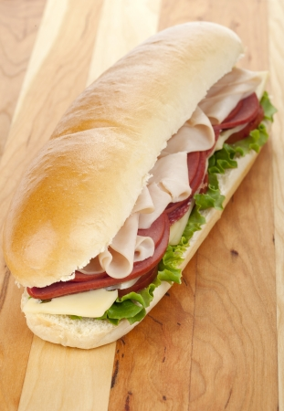 Appetizing ham and salami sandwich over a wooden background