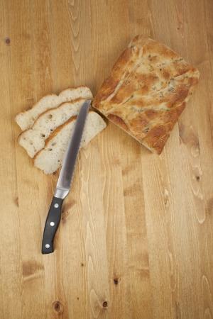 bread loaf: Vista dall'alto colpo di pagnotta di pane a fette e un coltello da pane su un tavolo di legno
