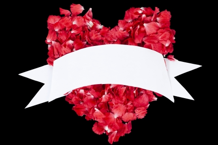 Heart shape red petals with a white ribbon over the dark background
