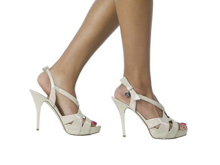 Walking feet wearing a white high heeled sandals Stock Photo - 17298026