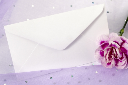 Horizontal image of white invitation card with a purple\ carnation flower on the side