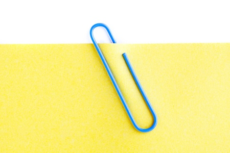 Close-up cropped shot of blue paperclip on yellow adhesive note. Stock Photo - 17302174