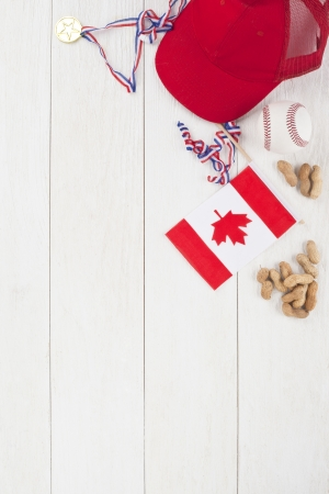 baseball stuff: Image of baseball stuff with Canadian flag and ground peanuts on a wooden table