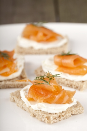 dill leaves: Selective focus on the biscuits with smoked salmon topped with dill leaves