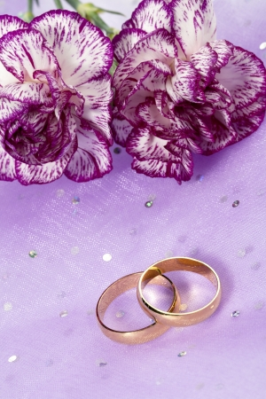 Cropped image of purple carnation with a wedding ring lying on the floor