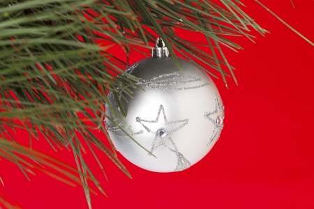 cele: Star shape Christmas bauble hanging on Christmas tree against red background. Stock Photo