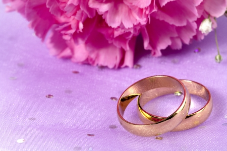 Golden wedding ring with a cropped image of pink flower on the background