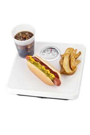 fattening: Junk foods with hotdog sandwich, French fries and cola on weighing scale, fattening concept