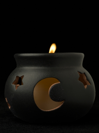 pot holder: Image of witch pot candle holder against black background