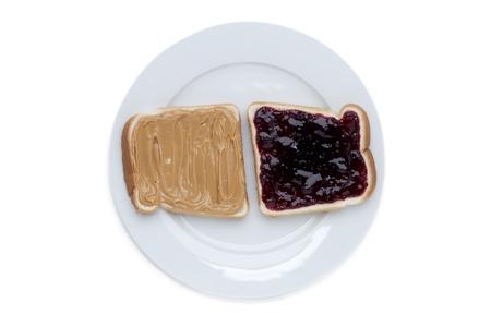 strawberry jam sandwich: Close up image of peanut and strawberry jam sandwich on white plate Stock Photo
