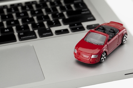 top down car: Close-up image of top down red toy car on the laptop isolated on a white surface Stock Photo