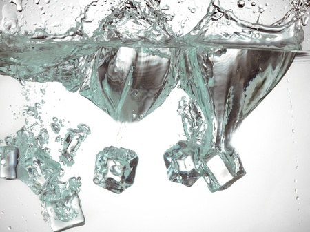 submerging: Ice cubes dropped into the water creating wave and splashes