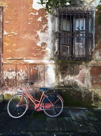 An orange bike leaning against a dirty wall Stock Photo - 17324259