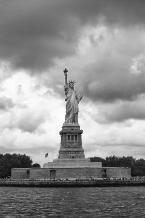 female likeness: Black and white image of Statue of Liberty against storm clouds.