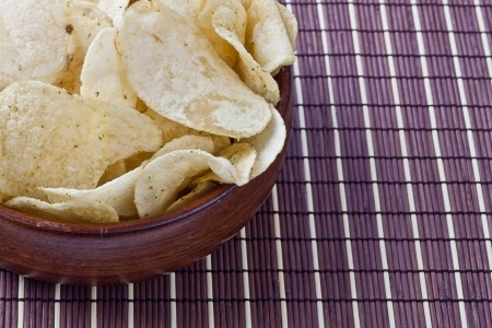 Cropped yummy potato chips placed in a traditional bowl