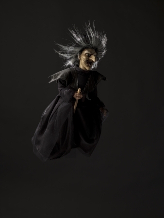 Witch riding on her broom over dark background. Stock Photo - 17324094