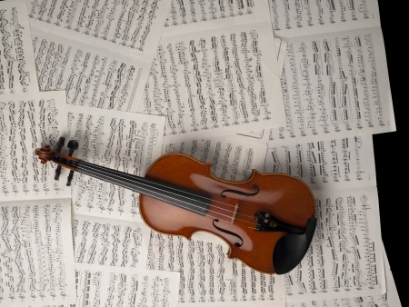 Overhead shot of a violin lying on the music sheets photo