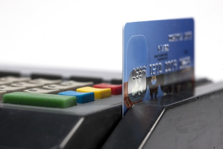 A blue credit-card in the swipe-slot of a machine. Stock Photo - 17324141